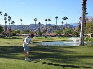 Sue takes an iron shot over water.