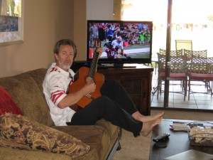 Rudy with guitar in front of TV