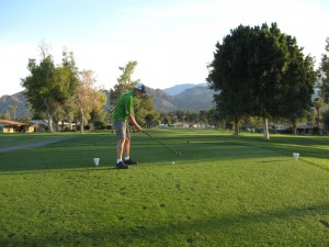 Rudy tees off at the 13th hole at Palm Desert Golf Club.