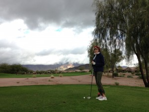 Sue in her 'winter' golfing outfit. The sun is trying to break through the clouds on the mountain.